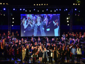 """The participants of """"The Women Who Score"""" gather on stage at the conclusion of the special Grand Performances concert. Photo: Sherry Barnett"""